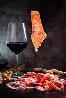 Jambon ibérique de bellota jambon ibérique jambon ibérique avec un verre de vin rouge