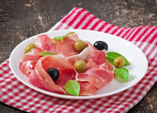 Jambon, olives, basilic sur vieux bois