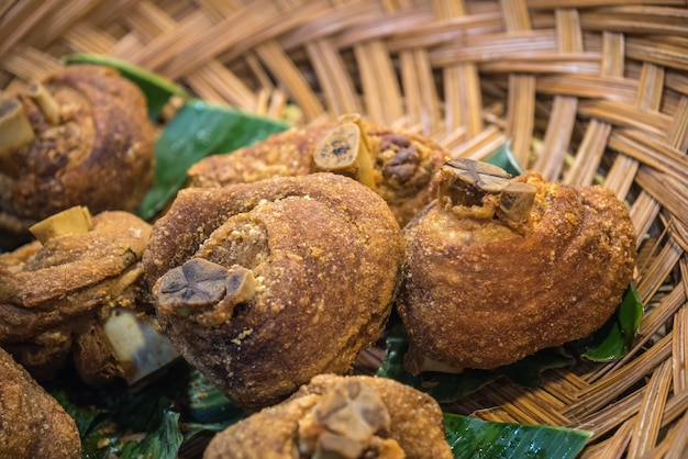 Jambon de porc croustillant (patte de porc frite croustillante) dans un panier traditionnel thaïlandais sur feuille de bananier