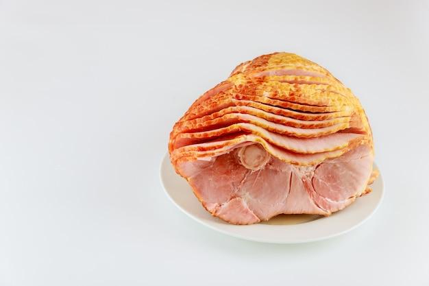 Jambon de porc fumé à l'hickory en spirale entière isolé sur fond blanc.