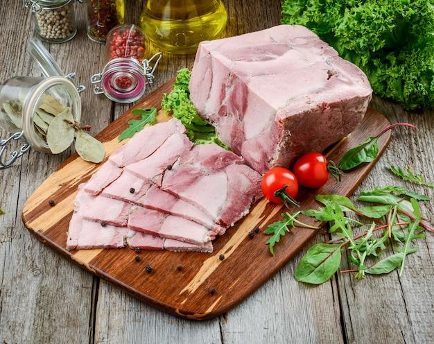 Jambon de porc rôti avec couteau de cuisine et légumes rôtis sur bois rustique foncé