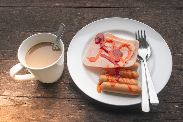 Jambon, saucisse et café sur un fond en bois