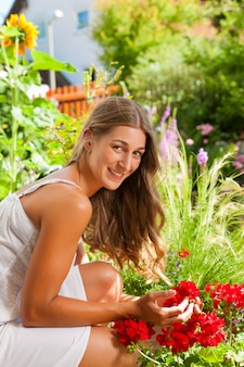 Jardin en été - femme heureuse avec des fleurs
