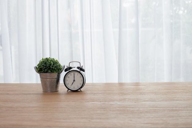 Jardin de feuilles vertes avec horloge rétro sur table en bois.