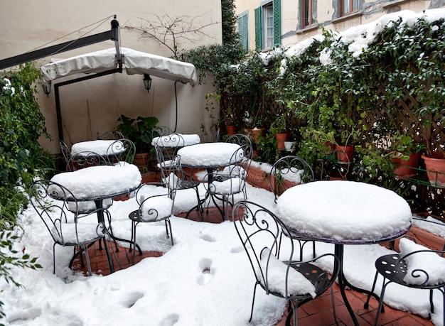 Jardin en hiver avec tables et chaises en fer forgé recouvertes de neige profonde.