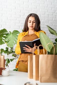 Jardinage domestique. petite entreprise. jeune femme jardinier prendre des notes dans le bloc-notes, ligne de sacs à provisions artisanales pour l'usine d'emballage à l'avant