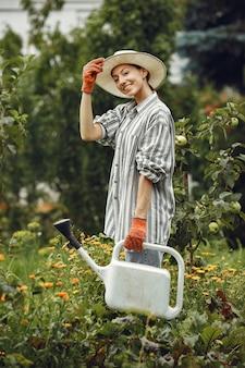 Jardinage en été. femme arrosage des fleurs avec un arrosoir. fille portant un chapeau.