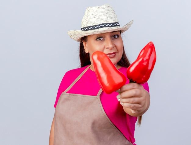 Jardinier d'âge moyen femme en tablier et chapeau montrant des poivrons rouges frais souriant confiant