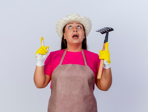 Jardinier d'âge moyen femme en tablier et chapeau portant des gants en caoutchouc tenant un mini râteau pointant vers le haut avec l'index d'être surpris
