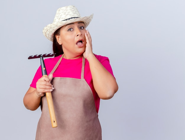 Jardinier d'âge moyen femme en tablier et chapeau tenant un mini râteau surpris
