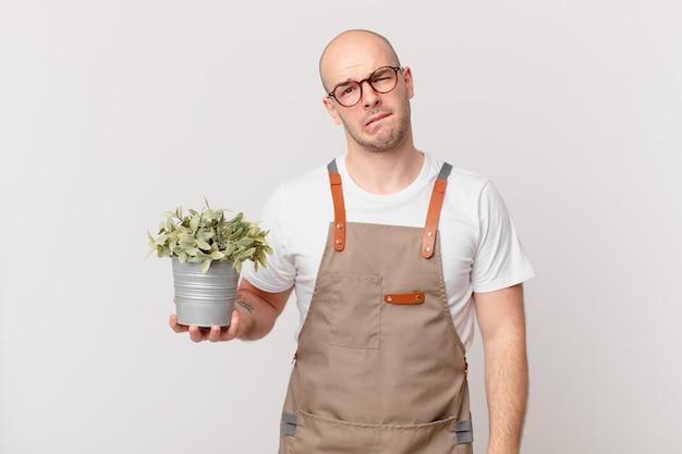Jardinier à l'air perplexe et confus, mordant la lèvre avec un geste nerveux, ne connaissant pas la réponse au problème