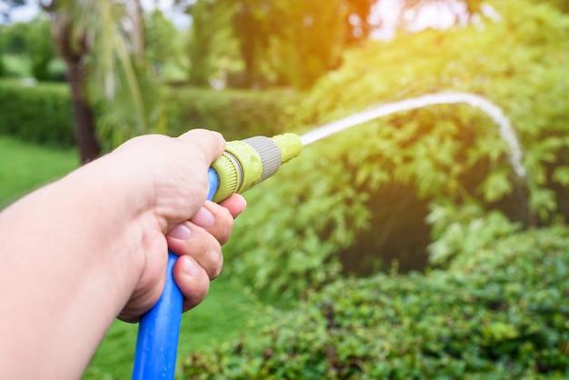 Jardinier arroser forme tuyau d'eau bleue dans le jardin
