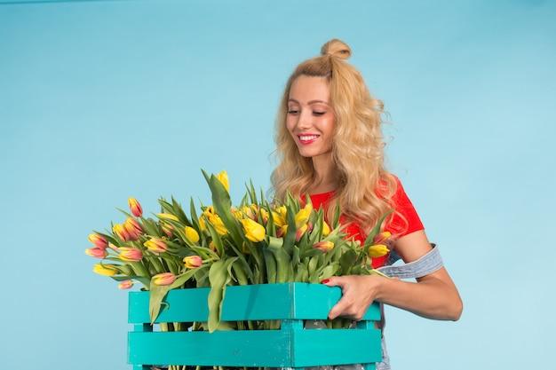 Jardinier de belle femme blonde tenant une boîte avec des tulipes sur un mur bleu