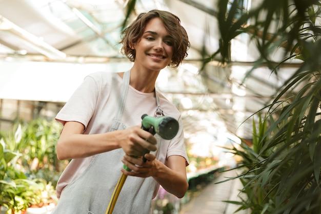 Jardinier de belle femme mignonne debout sur les plantes dans les fleurs d'eau à effet de serre