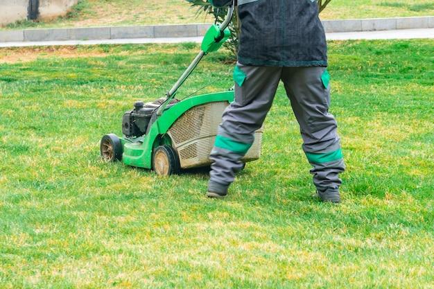Le jardinier coupant l'herbe par la tondeuse à gazon