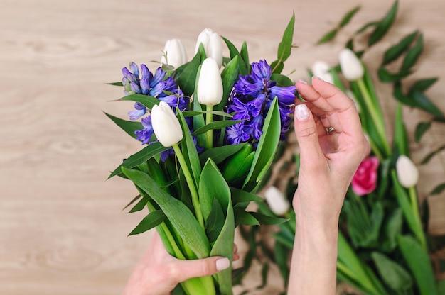Le jardinier dans le magasin de fleurs fait un bouquet. boutique de fleurs lifestyle. belle composition florale. détail.