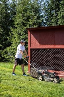 Jardinier fauchant l'herbe avec la tondeuse à gazon d'essence