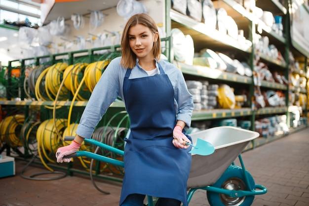 Jardinier femelle en tablier avec chariot de jardin en boutique pour les jardiniers. femme vend du matériel en magasin pour la floriculture, vente d'instruments de fleuriste