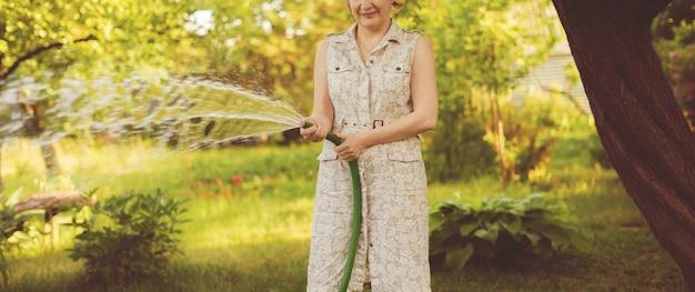 Jardinier féminin verser des plantes dans le jardin avec des tuyaux d'arrosage