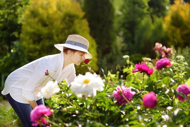 Jardinier femme d'âge moyen renifle pivoine fraîche.