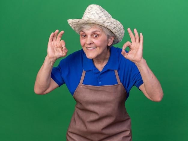 Jardinier femme âgée impressionné portant un chapeau de jardinage gesticulant signe ok avec deux mains