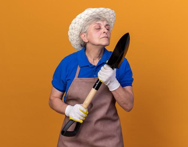 Jardinier femme âgée offensée portant un chapeau de jardinage tenant et regardant la pelle