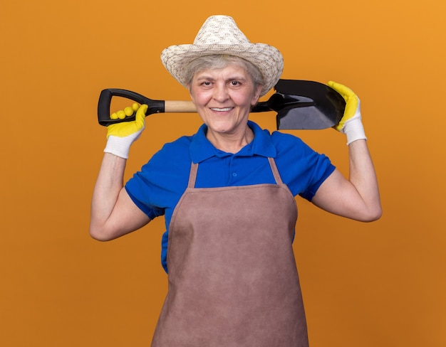 Jardinier femme âgée souriante portant un chapeau de jardinage et des gants tenant une pelle sur le cou derrière