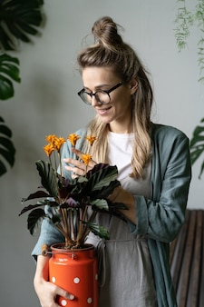Jardinier de femme en robe de lin, tenant une plante en fleurs de calathea en pot de lait rouge
