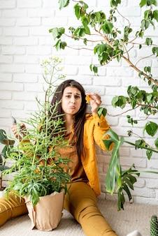 Jardinier femme travaillant dans le jardin d'accueil montrant des feuilles jaunes