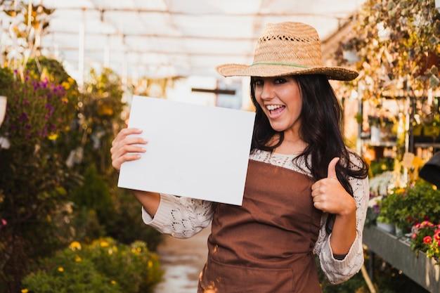 Jardinier avec feuille de papier gesticulant thumb-up