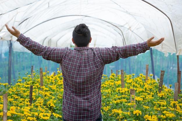 Jardinier gardant la fleur de souci dans le champ