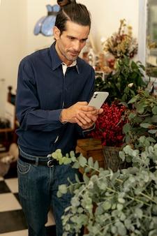 Jardinier homme aux cheveux longs photographiant les plantes