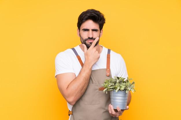 Jardinier homme avec barbe sur mur jaune isolé en pensant à une idée