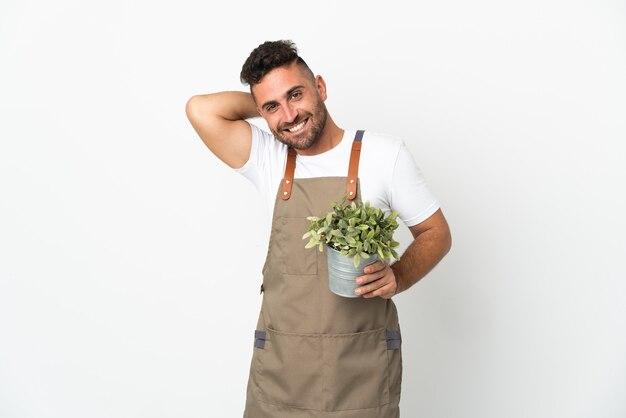 Jardinier homme tenant une plante sur fond blanc isolé en riant