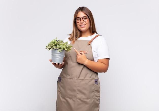 Jardinier de jeune femme souriant joyeusement, se sentant heureux et pointant vers le côté et vers le haut
