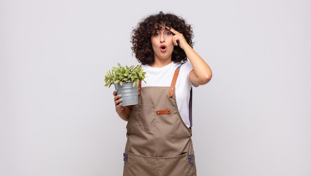 Jardinier de jeune femme à la surprise, la bouche ouverte, choquée, réalisant une nouvelle pensée, idée ou concept