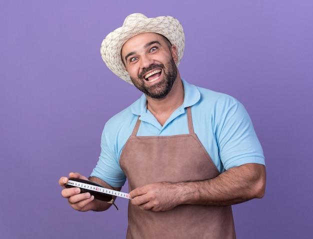 Jardinier mâle caucasien adulte excité portant un chapeau de jardinage mesurant l'aubergine avec un ruban à mesurer