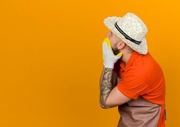 Jardinier mâle choqué portant chapeau et gants de jardinage met les mains sur la bouche à l'arrière