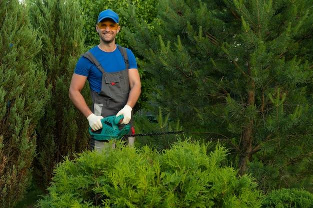 Le jardinier masculin dans un costume de protection élague les buissons avec une tondeuse électrique
