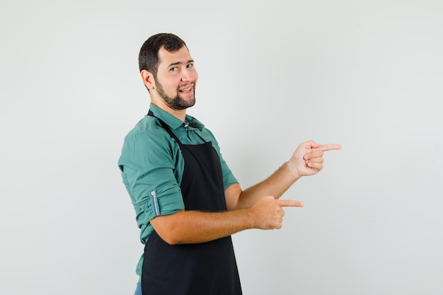 Jardinier masculin en t-shirt, tablier pointant sur le côté et semblant joyeux, vue de face.