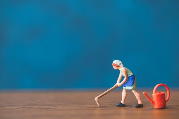 Jardinier de personnes miniature debout devant un fond de mur bleu