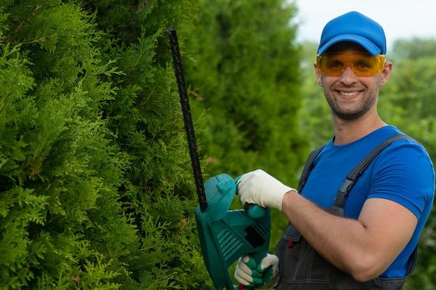 Un jardinier portant des lunettes de sécurité coupe et façonne une haie de thuya avec une tondeuse électrique