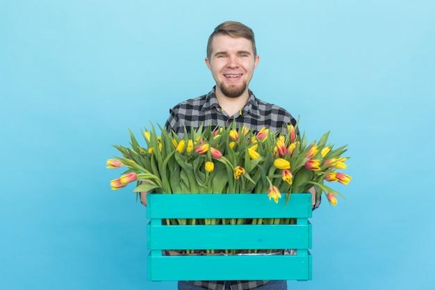Jardinier de race blanche avec boîte de tulipes en riant sur fond bleu