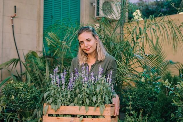 Jardinier souriant portant des pots de fleurs de lavande dans une caisse à la pépinière