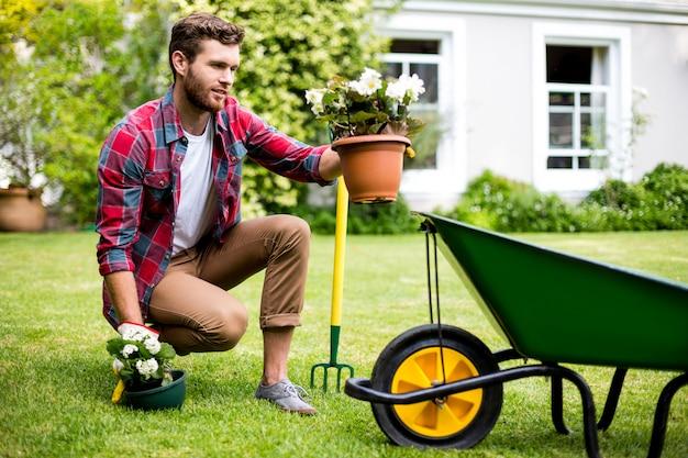 Jardinier tenant des plantes en pot dans la cour