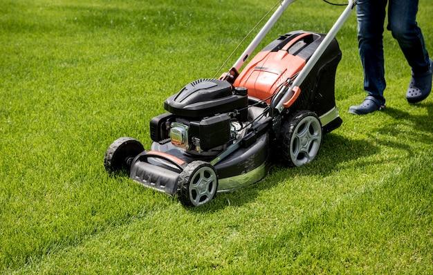 Jardinier tondant la pelouse. aménagement paysager. fond d'herbe verte