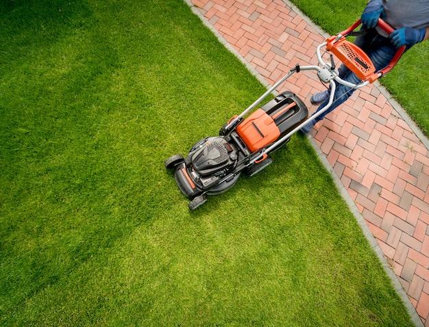 Jardinier tondant la pelouse. aménagement paysager.