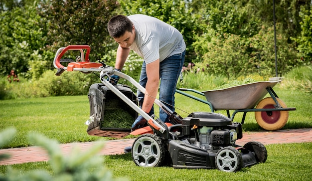 Jardinier vider l'herbe de la tondeuse à gazon dans une brouette après la tonte. aménagement paysager. jardinage