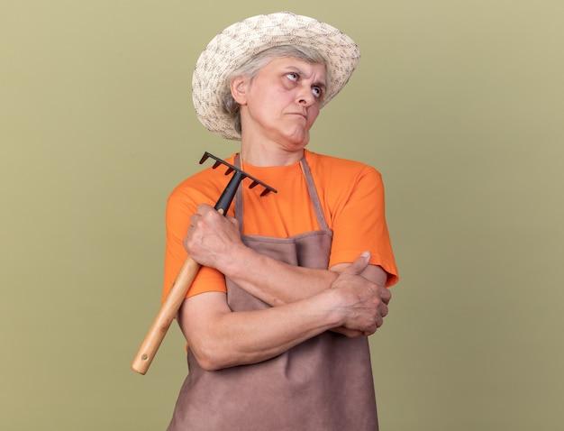 Jardinière âgée agacée portant un chapeau de jardinage tenant un râteau et levant isolé sur un mur vert olive avec espace pour copie