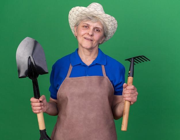 Une jardinière âgée confiante portant un chapeau de jardinage tient une pelle et un râteau